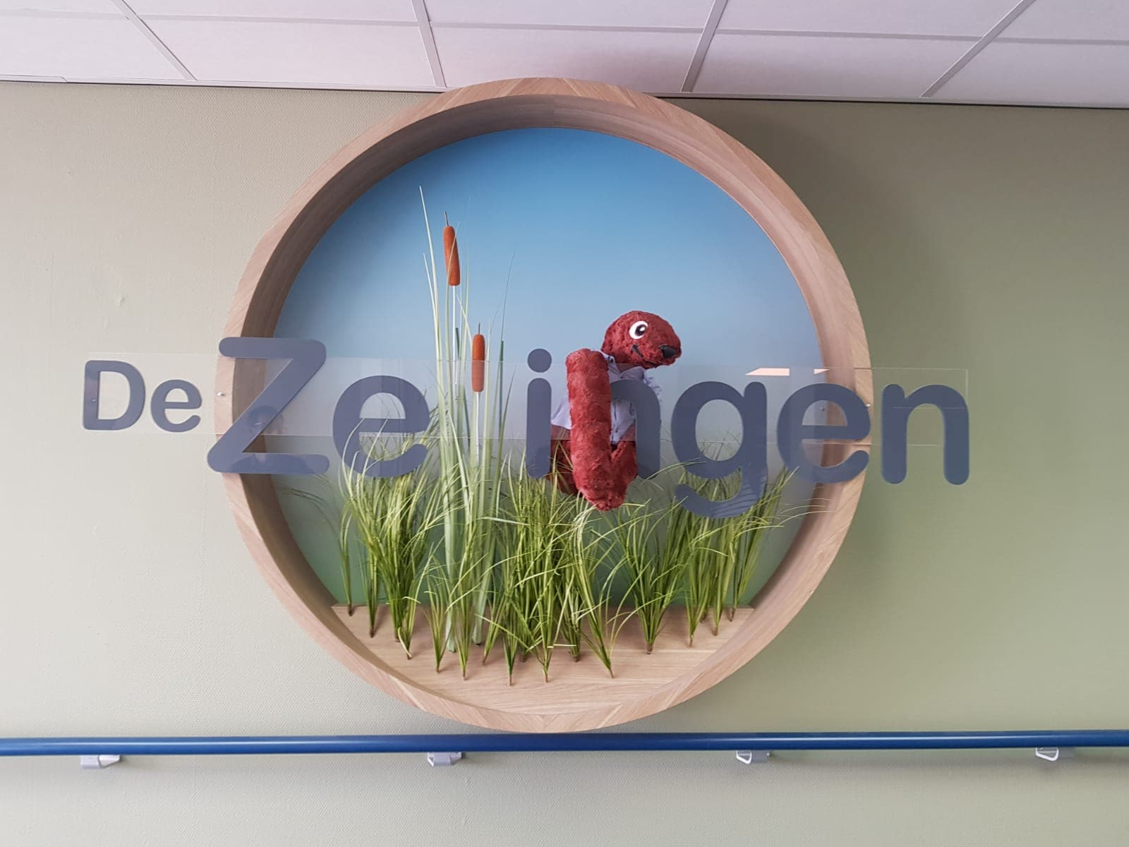 Sid hugging the big physical logo of the Zellingen located in the main hall.